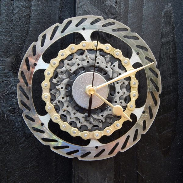 upcycled bicycle brake rotor and bicycle cassette parts wall clock, black and silver with gold hands and gold chain